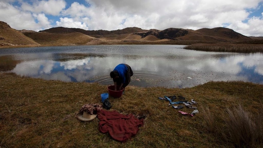 FILE - In this Aug. 19, 2012 file photo, Matilde Cruzado, 60, washes her clothes on the banks of the Namococha Lagoon in Combayo, Peru. A new law enacted July 11 by President Ollanta Humala weakens environmental protections in the Andean nation. Activists predict the weakened protections will spark more clashes between police who protect mines and highlanders angered by contamination and diminished water supplies they blame on the open pits. (AP Photo/Martin Mejia, File)