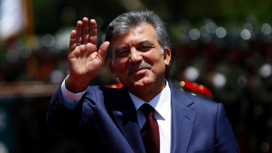 Turkey's President Abdullah Gul waves to the media after a review of a military guard of honor with Turkish Cypriot leader Dervis Eroglu, not pictured, in the Turkish Cypriot breakaway part of divided capital Nicosia in northern island of Cyprus, on Saturday, July 19, 2014. Gul arrived in the breakaway north to attend celebrations marking the 40th anniversary of Turkey's invasion of the east Mediterranean island following a coup by supporters of union with Greece. (AP Photo/Petros Karadjias)