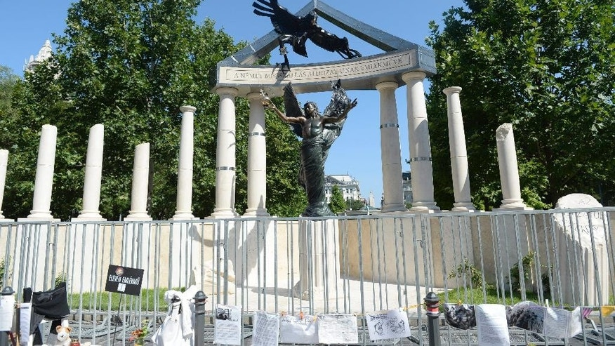 The new monument dedicated to the victims of the German occupation of Hungary during WW II is seen at Szabadsag (Liberty) square in downtown Budapest, Hungary, Sunday, July 20, 2014. In the middle of the night and guarded by police, workers have set up the main elements of the disputed memorial to the 1944 occupation of Hungary by Nazi Germany. The memorial meant to commemorate all victims of the German invasion, which also resulted in the deportation of over 430,000 Hungarian Jews to death camps like Auschwitz, has been widely criticized by Jewish groups and others, mainly because it is seen as an effort to downplay Hungarians' role in the Holocaust. (AP Photo/MTI, Noemi Bruzak)