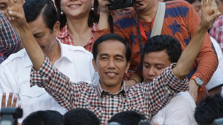 "This Wednesday, July 9, 2014 photo shows Indonesian presidential candidate Joko Widodo, popularly known as ""Jokowi"" gestures during his victory speech in Jakarta, Indonesia. After an ugly presidential election campaign, Indonesia is set to declare the winner on Tuesday - but that may not settle a simmering dispute between the two candidates, both of whom claim victory. (AP Photo/Dita Alangkara)"