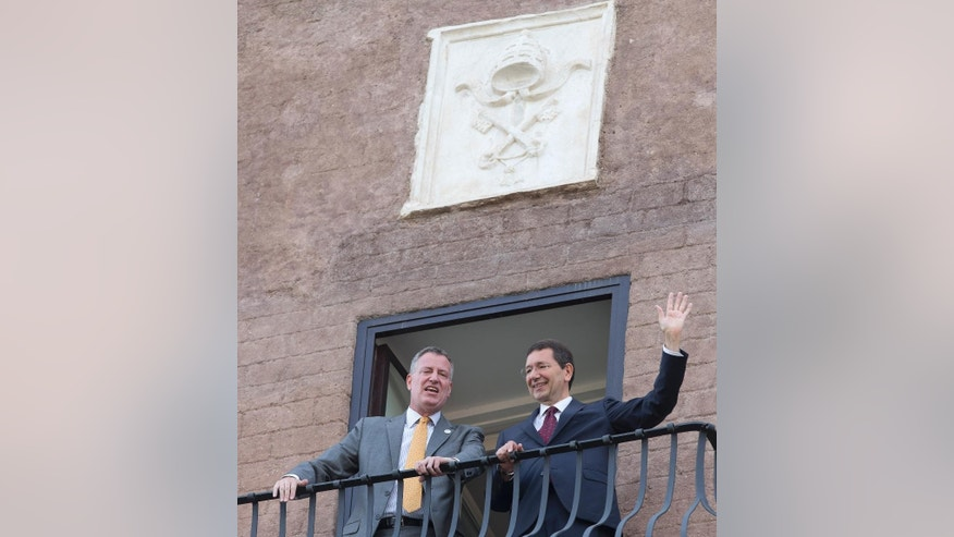 New York City Mayor Bill de Blasio, left, and Rome Mayor Ignazio Marino wave from a balcony of Rome's Campidoglio, Capitol Hill, overlooking the Roman Forum and Colosseum, Sunday, July 20, 2014. De Blasio and his family are in Italy for a family vacation. (AP Photo/Alessandra Tarantino)