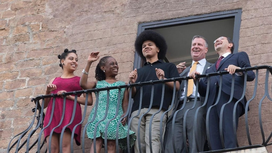 New York City Mayor Bill de Blasio, second from right, shares a laugh with Rome Mayor Ignazio Marino, right, as he is accompanied by his family, from left; daughter Chiara, wife Chirlane McCray, and son Dante, as the look out from a balcony of Rome's Campidoglio, Capitol Hill, overlooking the Roman Forum and Colosseum, Sunday, July 20, 2014. De Blasio and his family are in Italy for a family vacation. (AP Photo/Alessandra Tarantino)