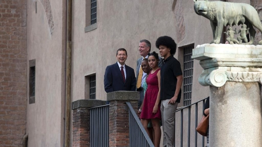 New York City Mayor Bill de Blasio, center, stands next to Rome's Mayor Ignazio Marino, left, as he is accompanied by his family, from right, son Dante, daughter Chiara, and wife Chirlane McCray, at Rome's Campidoglio, Capitol Hill, overlooking the Roman Forum and Colosseum, Sunday, July 20, 2014. De Blasio and his family are in Italy for a family vacation. At right is the statue, symbol of Rome, of the she-wolf feeding the founders of Rome, Romolo and Remo.  (AP Photo/Alessandra Tarantino)
