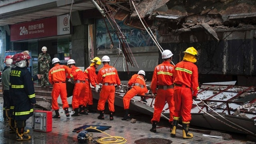 July 18, 2014: Rescuers try to remove a steel frame from a collapsed concrete roof which killed and injured a number of people after they took shelter during heavy rains in Shenzhen in south China's Guangdong province. (AP Photo)