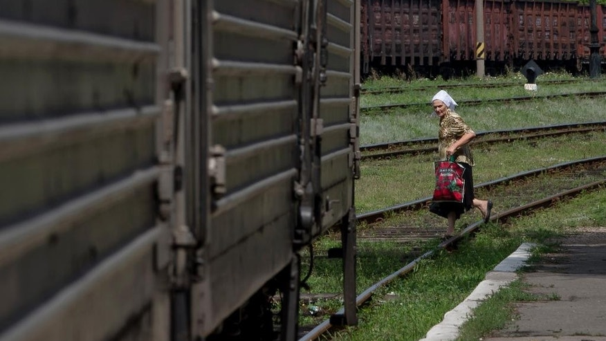 A woman looks at a refrigerated train loaded with the bodies of victims, in Torez, eastern Ukraine, 15 kilometers (9 miles) from  the crash site of Malaysia Airlines Flight 17, Sunday, July 20, 2014. Armed rebels forced emergency workers to hand over all 196 bodies recovered from the Malaysia Airlines crash site and had them loaded Sunday onto refrigerated train cars bound for a rebel-held city, Ukrainian officials and monitors said. (AP Photo/Vadim Ghirda)