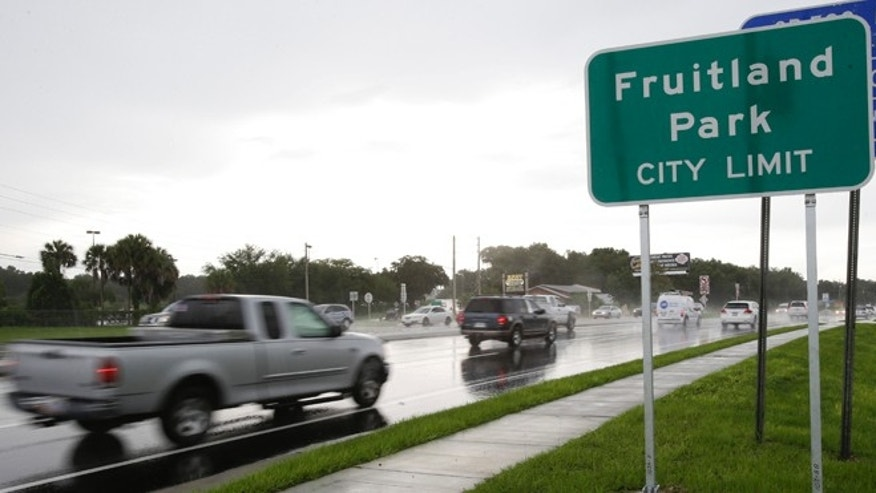 In this July 16, 2014 photo, cars pass by on a six lane highway that runs through Fruitland Park, Fla. Two police officers are no longer with the city department here after a law enforcement report tied them to the Ku Klux Klan. (AP Photo/John Raoux)