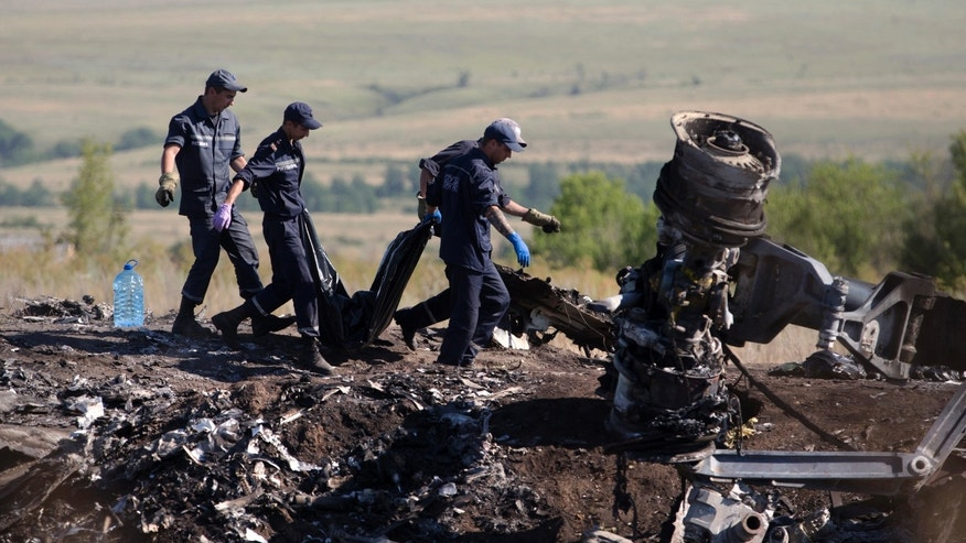 July 21, 2014 - Ukrainian Emergency workers carry a victim's body in a plastic bag at the crash site of Malaysia Airlines Flight 17 near the village of Hrabove, Donetsk region, eastern Ukraine.