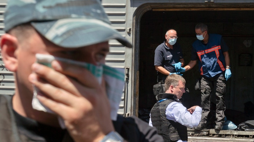 July 21, 2014 - A man covers his face with a rag due to the smell, as deputy head of the OSCE mission to Ukraine Alexander Hug, center right, stands outside a refrigerated train as members of Netherlands' National Forensic Investigations Team inspect bodies, seen in plastic bags, 9 miles from the crash site of Malaysia Airlines Flight 17, in Torez, eastern Ukraine.