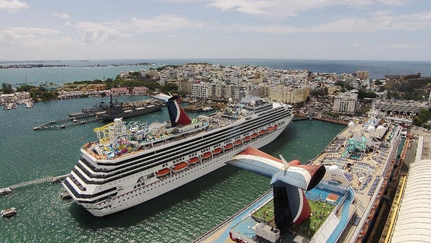 This July 16, 2014, photo, shows an aerial view of cruise ships docked at the Old San Juan pier in Puerto Rico.  A nearly eight-year recession has sent businesses and people fleeing to the mainland U.S. as the island tries to pay off billions billion in public debt. (AP Photo/Ricardo Arduengo)