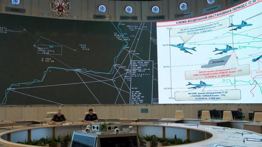 "Lieutenant-General Andrey Kartopolov, head of main operational department of Russian military's General Staff, left, speaks to the media during a news conference in Moscow, Monday, July 21, 2014. Russian officials offered evidence Monday, showing photos they said proved that Ukrainian surface-to-air systems were operating in the area in the days before the crash. Russian officials also offered evidence that a Ukrainian Sukhoi Su-25 fighter jet had flown ""between 3 to 5 kilometers (2 to 3 miles)"" from the Malaysia Airlines jet. Screens show traffic control recordings, left, and a scheme of air traffic over Donetsk, with Malaysia Airlines jet in the middle and unidentified military fighter jet next to it.  (AP Photo/Ivan Sekrtarev)"