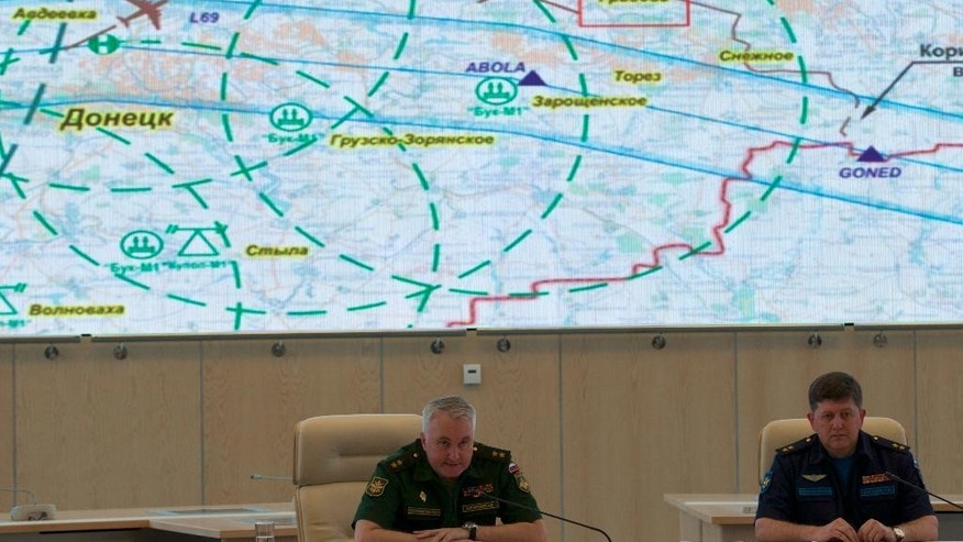 "Lieutenant-General Andrey Kartopolov, head of main operational department of Russian military's General Staff, center, speaks to the media during a news conference in Moscow, Monday, July 21, 2014. Russian officials offered evidence Monday, showing photos they said proved that Ukrainian surface-to-air systems were operating in the area in the days before the crash. Russian officials also offered evidence that a Ukrainian Sukhoi Su-25 fighter jet had flown ""between 3 to 5 kilometers (2 to 3 miles)"" from the Malaysia Airlines jet. Screen demonstrates the scheme of air traffic over Donetsk, Malaysia Airlines jet route and place of it's crash, red box, as well as Ukrainian antiaircraft missile launchers positions. At right is Igor Makushev, chief of Russia's Air Force general staff. (AP Photo/Ivan Sekrtarev)"