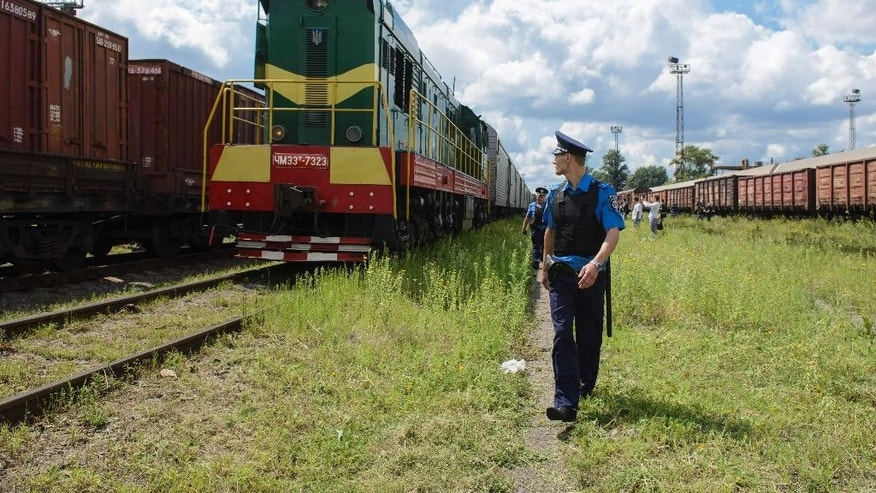 Police officers secure a refrigerated train loaded with bodies of the passengers of Malaysian Airlines flight MH17 as it arrives in a Kharkiv factory for a stop on Tuesday, July 22, 2014. The train carrying the remains of people killed in the Malaysia Airlines crash arrived in the eastern Ukrainian city of Kharkiv on Tuesday on their way to the Netherlands, a journey which has been agonizingly slow for relatives of the victims. (AP Photo/Olga Ivashchenko)