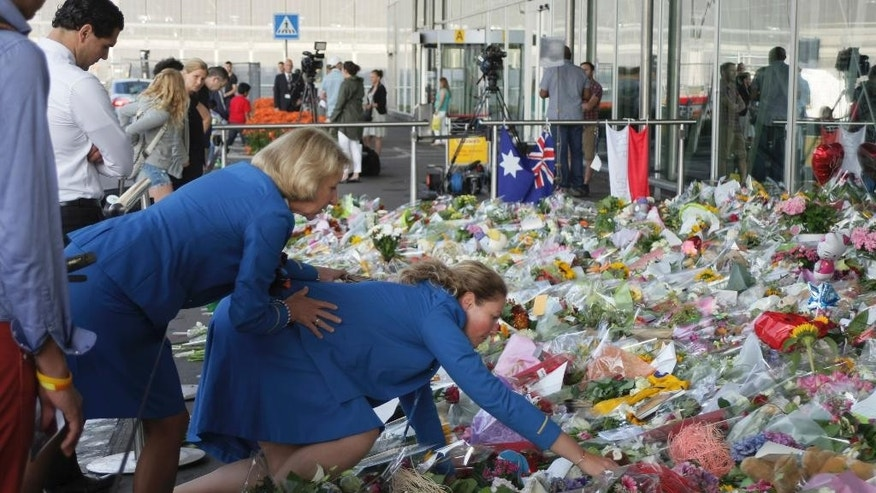 "Two KLM cabin crew reach out into a sea of flowers at Schiphol airport in Amsterdam, Tuesday, July 22, 2014. A train carrying the remains of people killed in the Malaysia Airlines crash arrived in the eastern Ukrainian city of Kharkiv on Tuesday on their way to the Netherlands. Oleksander Kharchenko, spokesman for the state committee on the crash, said ""we will do our best"" to send the bodies to the Netherlands on Tuesday. Ukraine has agreed to send remains of all the victims there for identification and forensic investigation. (AP Photo/Mike Corder)"