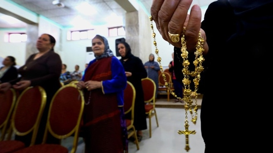 July 19, 2014: In this photo, displaced Christians who fled the violence in Mosul, pray at Mar Aframa church in the town of Qaraqoush on the outskirts of Mosul, Iraq. (AP)