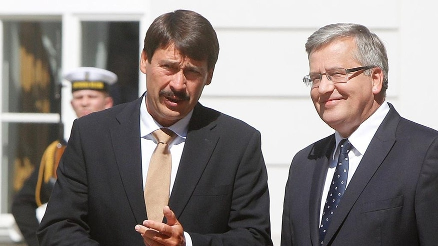 Poland's President Bronislaw Komorowski, right, welcomes Hungary President Janos Ader, left, during a welcome ceremony at the Presidential Palace in Warsaw, Poland, Tuesday, July 22, 2014. Presidents of the Baltic States, the Visegrad Group, Romania and Bulgaria attend the regional summit to discuss the September NATO Summit in Newport. (AP Photo/Czarek Sokolowski)