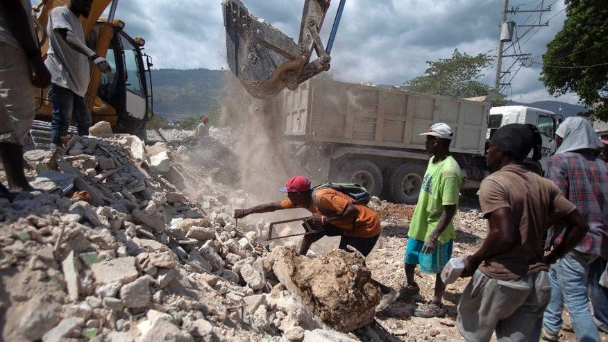 "In this July 10, 2014, photo, men search for items to recover in the rubble of houses razed by bulldozers in downtown of Port-au-Prince, Haiti. Demolitions began in June for construction of the ""administrative city"" in downtown Port-au-Prince. But the plan hailed as a sign of post-quake rebirth by some residents has also set off a firestorm of criticism for creating a new wave of homelessness after many poor renters were given just minutes to vacate their dwellings before bulldozers arrived.  ( AP Photo/Dieu Nalio Chery)"