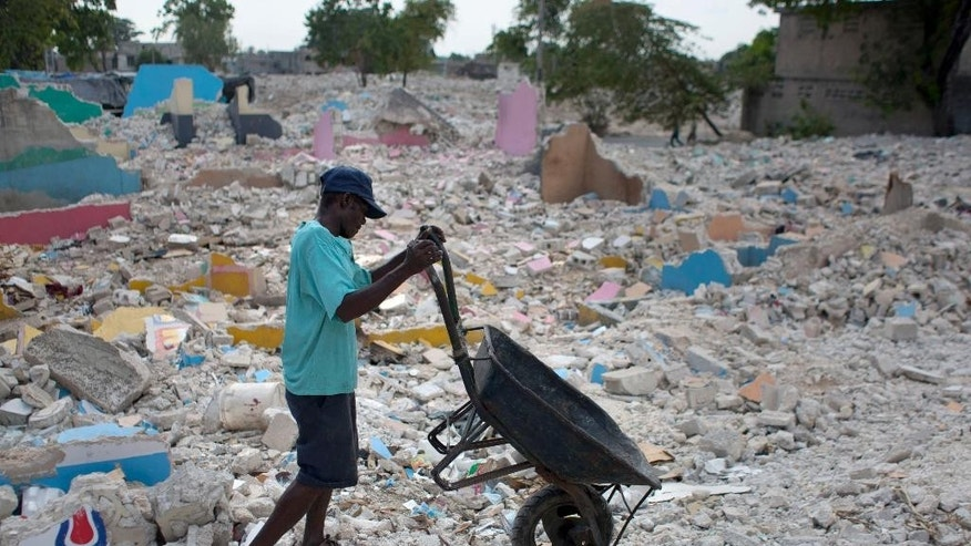 In this July 11, 2014, photo, a man takes his wheelbarrow through the rubble of houses razed by bulldozers in downtown of Port-au-Prince, Haiti. While there are no available figures as to the number of people left homeless by the demolitions, the city center has become dotted with new encampments of tarp shacks in recent weeks. ( AP Photo/Dieu Nalio Chery)