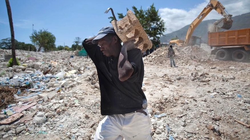 In this July 10, 2014, photo, a man carries a cinder block after taking it from the rubble of houses razed by bulldozers in downtown of Port-au-Prince, Haiti. Hills of rubble left by the bulldozers have grown so large that it almost looks like a fresh quake just hit the city. (AP Photo/Dieu Nalio Chery)