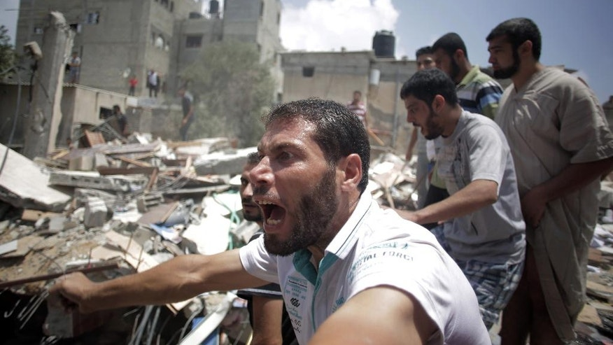 FILE - In this Monday, July 21, 2014, file photo, a Palestinian overcome by emotion watches rescuers carry a body from the rubble of a house which was destroyed by an Israeli missile strike, in Gaza City. Disagreement over whether to lift the Gaza blockade is a key stumbling block to ending more than two weeks of fighting between the Islamic militant Hamas and Israel. Some in Gaza say they would rather endure more fighting than return to life under blockade. (AP Photo/Khalil Hamra, File)