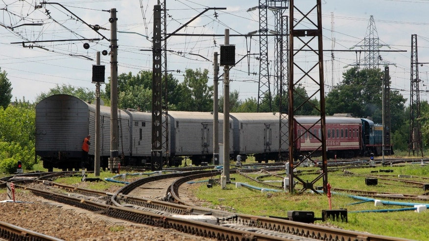 A refrigerated train loaded with bodies of the passengers of Malaysian Airlines flight MH17 departs Kharkiv railway station, Ukraine, Tuesday, July 22, 2014. The train carrying the remains of people killed in the Malaysia Airlines crash arrived in the eastern Ukrainian city of Kharkiv on Tuesday on their way to the Netherlands, a journey which has been agonizingly slow for relatives of the victims. (AP Photo/ Sergei Chizavkov)