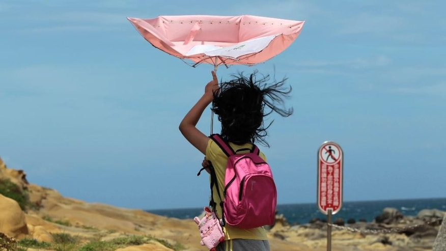 A girl struggles with winds from approaching Typhoon Matmo along the eastern coast of Keelung, northeastern Taiwan, Tuesday, July 22, 2014. The eye of Typhoon Matmo is expected to make landfall in eastern Taiwan early Wednesday bringing heavy rain and winds with gusts over 130 kilometers (85 miles) per hour. (AP Photo/Wally Santana)