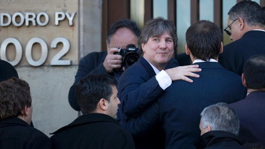 FILE - In this June 9, 2014 file photo, Argentina's Vice President Amado Boudou looks back as he enters a federal court in Buenos Aires, Argentina. The Vice President is back in court, this time over false data in the papers of an old car that he bought about 20 years ago. Boudou appeared before a federal judge Wednesday, July 23, 2014, and presented a written statement instead of speaking on his defense. Boudou is accused of transferring a Honda CRX automobile to his name irregularly in 2003. (AP Photo/Natacha Pisarenko, File)