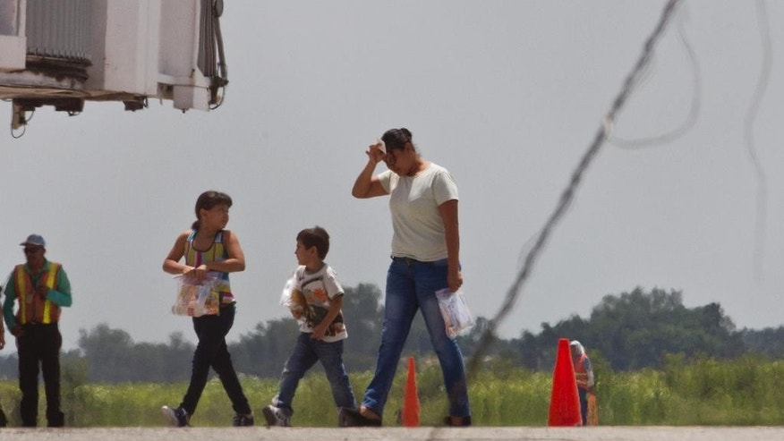 In this Friday, July 18, 2014 photo, deportees Elsa Ramirez, 27, and her two children, Sandra, 8, and Cesar, 5, walk on the tarmac after arriving from the United States, at the airport in San Pedro Sula, Honduras. Ramirez fled with her two children the violence that killed her husband and two brothers, fearing she was next. But with the Obama administration's expedited deportation of Central American families, she was flown back to where she started, the heart of Honduras' drug-trafficking country, where she is hiding from her husband's murderers and wondering what's next. (AP Photo/Esteban Felix)