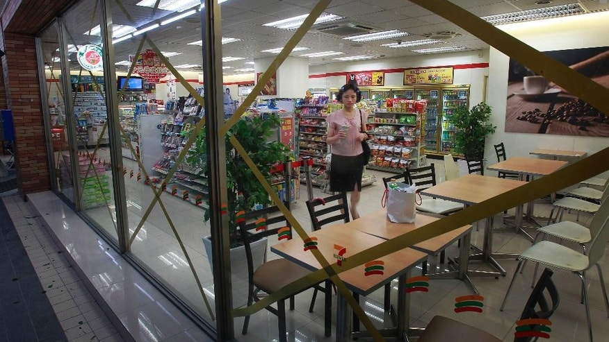 A woman has breakfast at a convenience store behind tape-reinforced glass as Typhoon Matmo passes Taipei, Taiwan, Wednesday, July 23, 2014. The eye of Typhoon Matmo made landfall in eastern Taiwan early Wednesday bringing with it heavy rains and winds with gusts over 140 kilometers (85 miles) per hour. (AP Photo/Wally Santana)