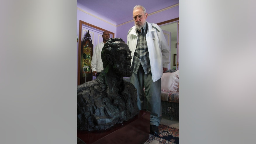 Cuba's Fidel Castro looks at a sculpture of himself, a gift from China's President Xi Jinping in Havana, Cuba, Tuesday, July 22, 2014. Xi Jinping said that his state visit to Cuba is aimed at carrying forward the traditional friendship between the two countries jointly built by Castro and the older generations of Chinese leaders. He also extended good wishes to Castro for his upcoming 88th birthday. (AP Photo/Alex Castro)