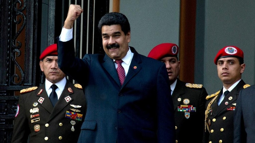 Venezuela's President Nicolas Maduro, kenter, greets supporters as he waits for  China's President Xi Jinping outside of National pantheon in Caracas, Venezuela, Sunday, July 20, 2014. Xi Jinping is in Venezuela for a two day official visit. (AP Photo/Fernando Llano)