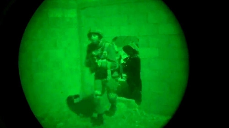 FILE - In this file image, made from video shot through a night vision scope, provided by the Israeli military on Friday, July 18, 2014, troops move through an opening in a wall during the early hours of a ground attack in the Gaza Strip. Beyond the boom of Israeli airstrikes and the stream of rockets fired from Gaza, Israel and Hamas are also battling to control the message emanating from this latest Israeli-Palestinian conflagration. Using videos, Twitter, text messages, leaflets and phone calls, both sides have attempted to direct the tone of the fighting. (AP Photo/Israeli Defense Forces, File)