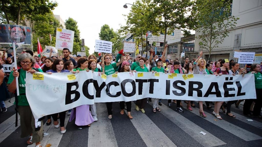 Pro-Palestinian demonstrators hold a banner and shout slogans, in Paris, France, Wednesday, July 23, 2014 during a demonstration to protest against the Israeli army's shelling in the Gaza strip. Protesters marched through Paris against the Israel-Gaza war under the watch of hundreds of police in an authorized  demonstration days after two banned  protests degenerated into urban violence.(AP Photo/Francois Mori )
