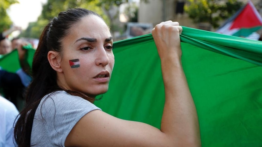 A pro-Palestinian demonstrator with a Palestinian flag on her cheek shouts slogans, in Paris, France, Wednesday, July 23, 2014 during a demonstration to protest against the Israeli army's shelling in the Gaza strip. Protesters marched through Paris against the Israel-Gaza war under the watch of hundreds of police in an authorized  demonstration days after two banned  protests degenerated into urban violence.(AP Photo/Francois Mori )