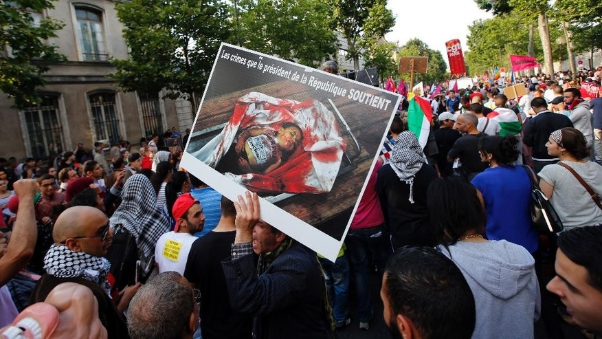 "Pro-Palestinian demonstrators hold a picture with a text reading ""The Crime that The French President supports"", in Paris, France, Wednesday, July 23, 2014 during a demonstration to protest against the Israeli army's shelling in the Gaza strip. Protesters marched through Paris against the Israel-Gaza war, under the watch of hundreds of police in an authorized  demonstration days after two banned protests degenerated into urban violence.(AP Photo/Francois Mori )"