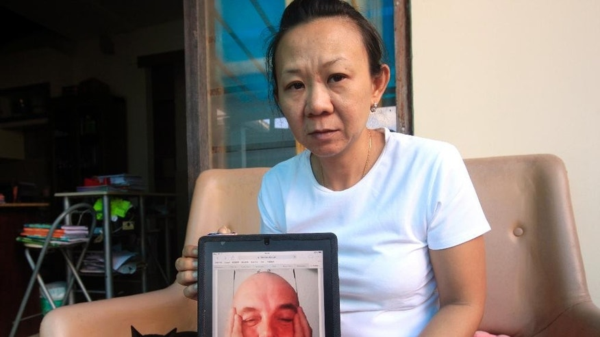 Indonesian Christine holds a portrait of her fiance Willem Grootscholten of the Netherlands who was a passenger of the crashed Malaysia Airlines Flight 17, at her guesthouse in Bali, Indonesia, Wednesday, June 23, 2014. The passenger plane was shot down over eastern Ukraine with the loss of 298 lives. (AP Photo/Firdia Lisnawati)
