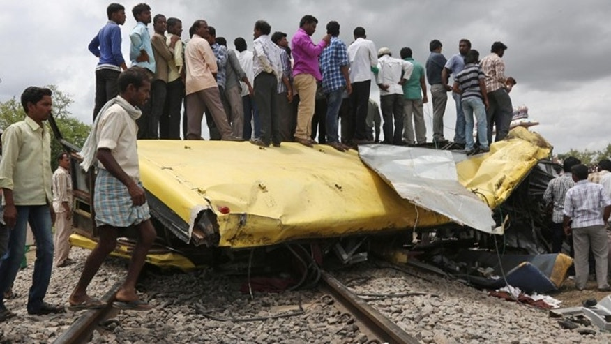 July 24, 2014: Indians stand on top of a bus that was crushed when a train crashed into it in Medak district in the southern Indian state of Telangana.