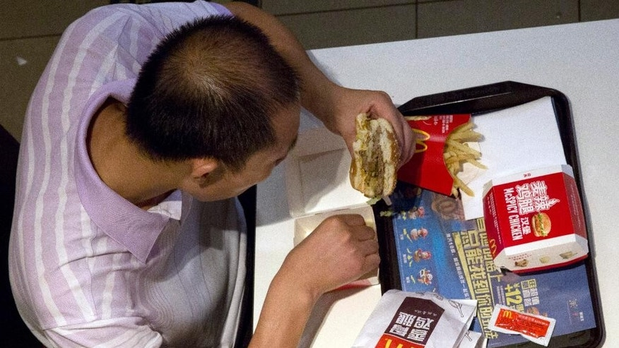A man eats a burger at a McDonald's restaurant in Beijing Tuesday, July 22, 2014. China's food safety agency on Tuesday announced a nationwide inspection of processing factories and meat suppliers used by a company accused of selling expired beef and chicken to McDonald's and KFC. (AP Photo/Ng Han Guan)