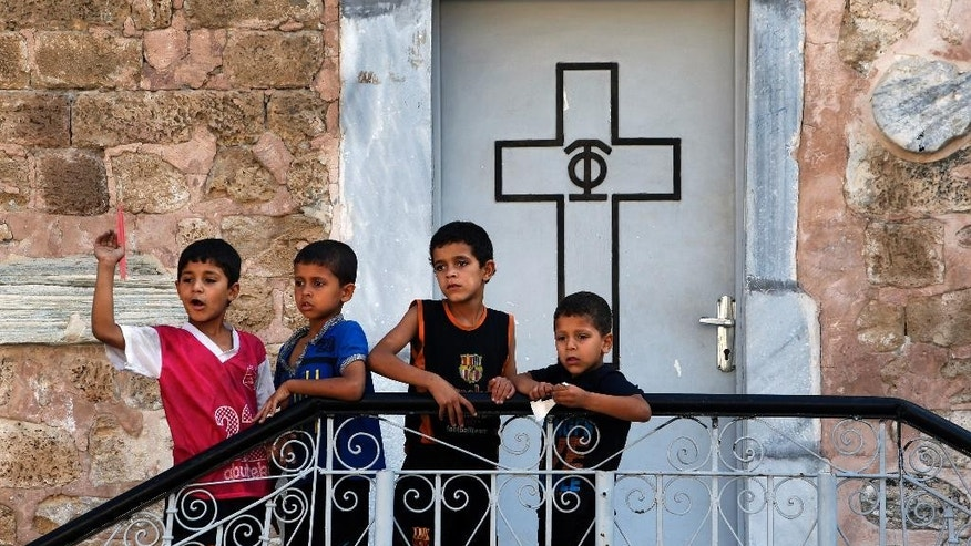 Palestinian boys play on the grounds of the St. Porphyrios Church in Gaza City, Wednesday, July 23, 2014. St. Porphyrios Church has thrown its doors open to hundreds of displaced Palestinians. (AP Photo/Lefteris Pitarakis)