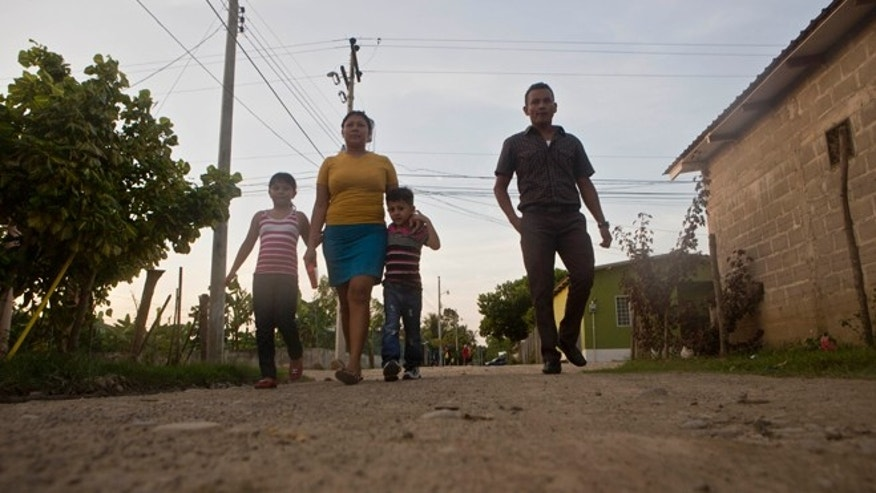 Deportee Elsa Ramírez walks with her children Sandra, César Ramos, and her brother Elvin Ramírez in Tocoa, Honduras.