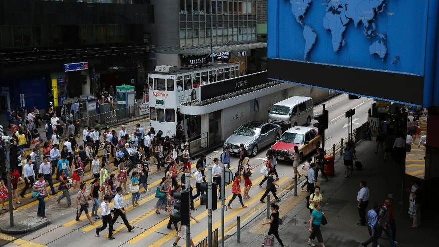Pedestrians cross the main street in Central, Hong Kong's business district, Thursday, July 24, 2014. As activists vow to shut down the financial district in protest at China's attempt to hobble democratic elections in the city, businessman Bernard Chan is preparing for the worst. Chan's investment company has added backup phone lines, bought extra laptops and stockpiled instant noodles in case its headquarters downtown is caught in the middle of the protest. (AP Photo/Kin Cheung)