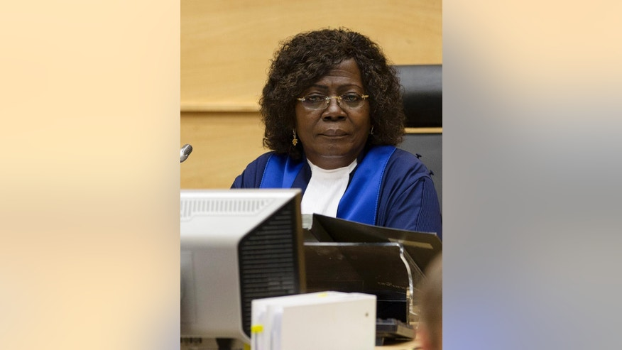 Judge Kuenyehia from Ghana enters the courtroom of the International Criminal Court (ICC) in The Hague, Netherlands, Thursday, July 24, 2014. Appeals judges at the ICC have upheld a decision to allow a Moammar Gadhafi-era intelligence chief to be put on trial in Libya. The appeals panel ruled Thursday that the case against Abdullah al-Senoussi should not be handled by the Hague-based court because prosecutors in Libya are pursuing similar charges against him. The ICC indicted Al-Senoussi in 2011 on crimes against humanity charges of murder and persecution allegedly commited during Gadhafi's unsuccessful attempt to put down a popular revolt against his regime. Al-Senoussi is currently in detention in Libya. (AP Photo/Michael Kooren, Pool)