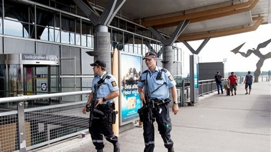 "July 24: Armed Police patrol outside the terminal building at Oslo Airport. Norway's intelligence service says it has been warned of an imminent ""concrete threat"" against the nation from people with links to Islamic fighters in Syria."