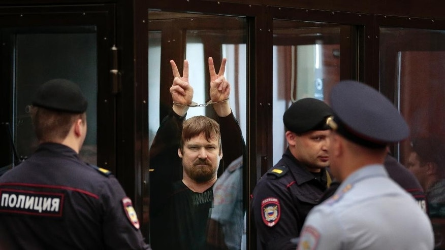 Russian opposition activist Leonid Razvozzhayev, in handcuffs, shows V-signs from a defendant's cage in a court room prior to a hearing in the Bolotnaya square protest trial in Moscow, Russia, Thursday, July 24, 2014.  Sergei Udaltsov and Leonid Razvozzhayev are waiting for the sentence Thursday in the Moscow city court on charges of organizing mass riots and colluding to commit a crime. They both pleaded not guilty in a trial that has dragged on since October 2012, when they were detained and put under house arrest. (AP Photo/Ivan Sekretarev)