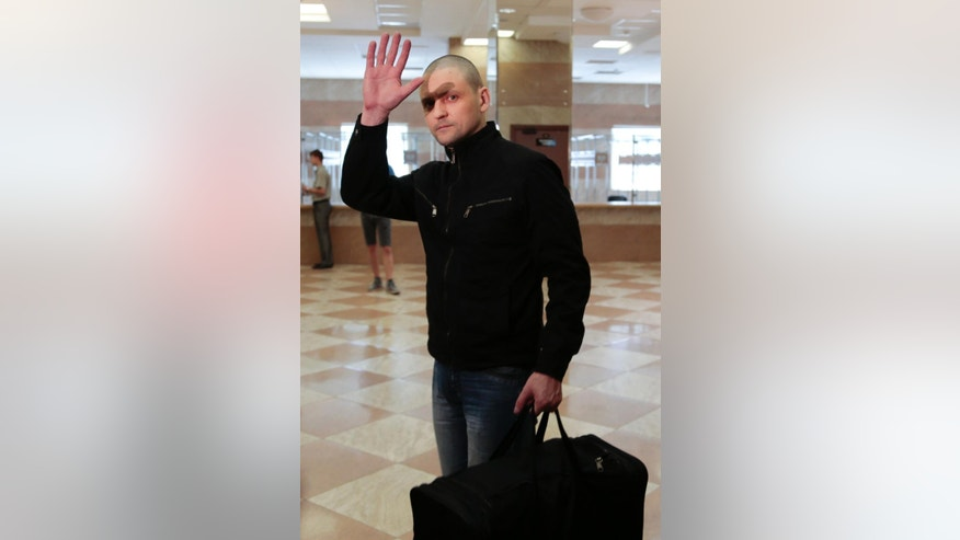 Russian opposition activist Sergei Udaltsov, holds his belongings, and waves good-bye in a court hall prior to a hearing for the Bolotnaya square protest, in Moscow, Russia, Thursday, July 24, 2014.  Sergei Udaltsov and Leonid Razvozzhayev are waiting for the sentence Thursday in the Moscow city court on charges of organizing mass riots and colluding to commit a crime. They both pleaded not guilty in a trial that has dragged on since October 2012, when they were detained and put under house arrest. (AP Photo/Ivan Sekretarev)