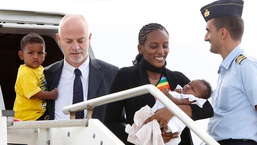 July 24, 2014: Meriam Ibrahim disembarks with her children Maya, in her arms, and Martin, accompanied by Italian deputy Foreign Minister Lapo Pistelli, after landing at Ciampino's military airport on the outskirts of Rome. (AP Photo/Riccardo De Luca)