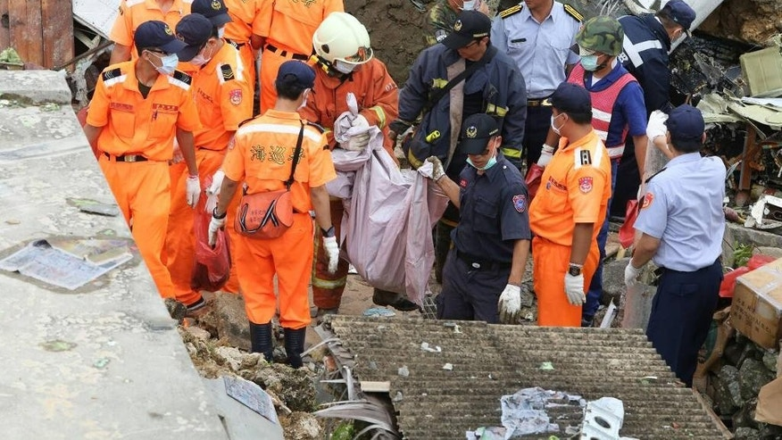 Rescue workers survey the wreckage of TransAsia Airways Flight GE222 which crashed on the Taiwanese island of Penghu Thursday, July 24, 2014. The plane attempting to land in stormy weather crashed on the island late Wednesday, killing more than 40 people and wrecking houses and cars on the ground. (AP Photo) TAIWAN OUT