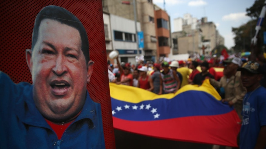 CARACAS, VENEZUELA - MARCH 06:  A portrait of former Venezuelan President Hugo Chavez looks on as government supporters march on March 6, 2014 in Caracas, Venezuela. Pro-government organiztions have organized marches in response to widespread opposition demonstrations over the last three weeks.  (Photo by John Moore/Getty Images)
