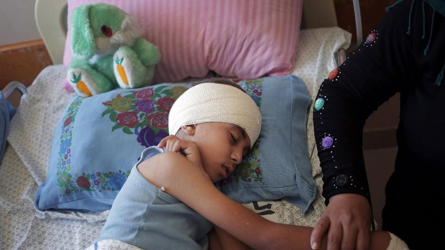In this Thursday, July 24, 2014 photo, Mojahed al-Ejla, 8, rests at the Shifa hospital where he is receiving treatment for a fractured skull caused by a July 19 Israeli shelling while he and the family were fleeing from the Shijaiyah neighborhood, in Gaza City. The pediatrics wing of the largest hospital in the Gaza Strip is filled with the youngest victims of more than two weeks of Israel-Hamas fighting. (AP Photo/Khalil Hamra)