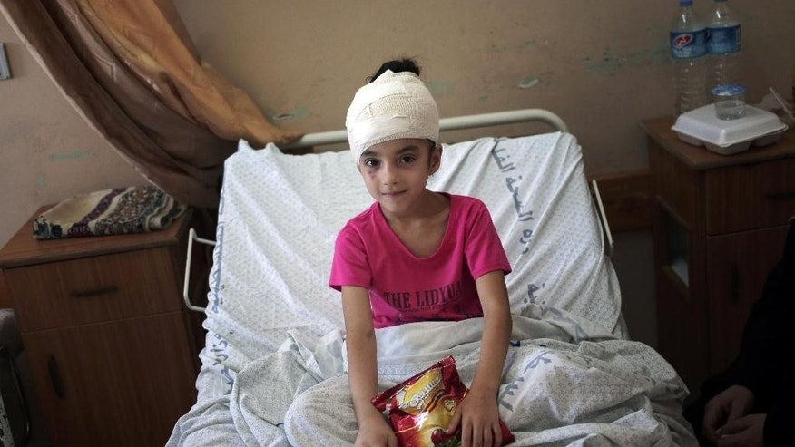 In this Thursday, July 24, 2014 photo, Shahd al-Henawi, 8, sits in her bed at the Shifa hospital, where she is receiving treatment for a fractured skull caused by a partial collapse of the family house following a July 23 Israeli strike at the Jebaliya refugee camp in the northern Gaza Strip, in Gaza City. The United Nations says civilians make up three-fourth of the dead and a majority of the wounded in the 18 day-old Israel-Hamas war. (AP Photo/Khalil Hamra)