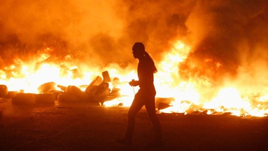 July 24, 2014: A Palestinian protester walks next to burning tyres during clashes with Israeli troops, at a protest against Israeli offensive in Gaza, at Qalandia checkpoint near the West Bank city of Ramallah.